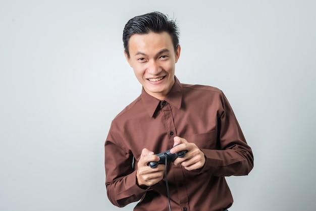 Młody azjatykci mężczyzna bawić się wideo grę z joystickiem, szczęśliwy uczucie.