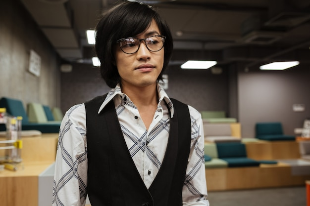 Młody azjatykci mężczyzna jest ubranym szkła patrzeje na boku.