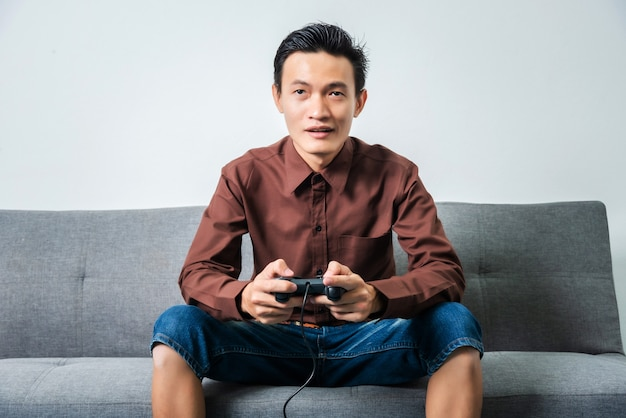 Młody azjatykci mężczyzna mienia joystick dla bawić się piłki nożnej wideo grę podczas gdy siedzący na kanapie w żywym pokoju.