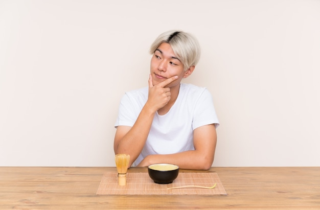 Młody azjatykci mężczyzna myśleć matcha z matcha herbatą w stole