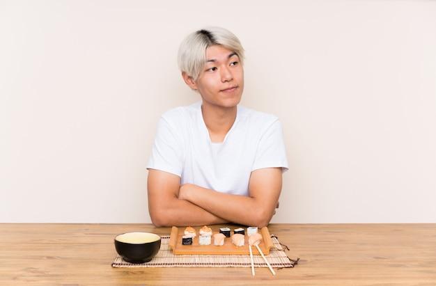 Młody azjatykci mężczyzna myśleć pomysł z suszi w stole
