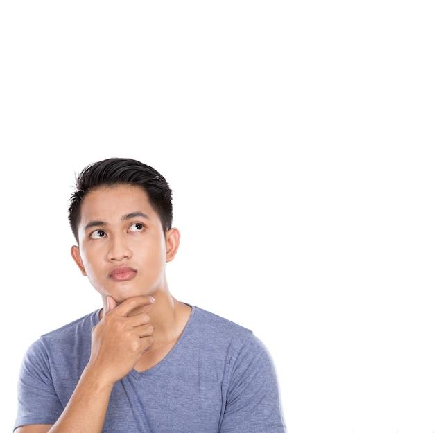 Młody azjatykci mężczyzna myśleć przyglądający up odizolowywający