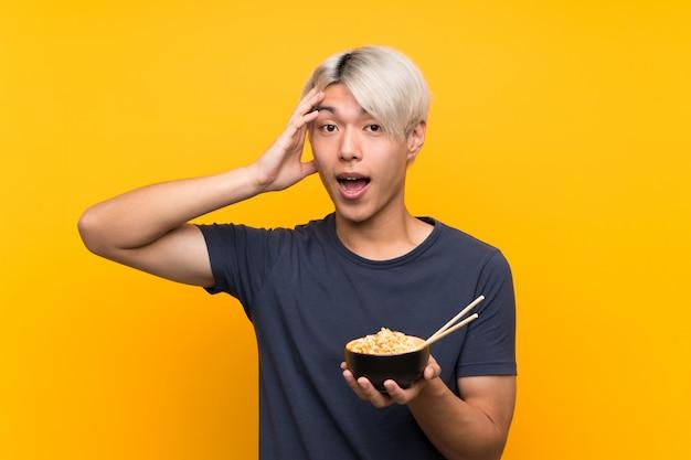 Młody azjatykci mężczyzna nad odosobnionym kolorem żółtym z niespodzianką i szokującym wyrazem twarzy