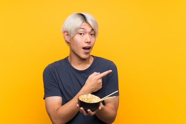 Młody azjatykci mężczyzna nad odosobnionym kolorem żółtym zaskakującym i wskazuje stronę