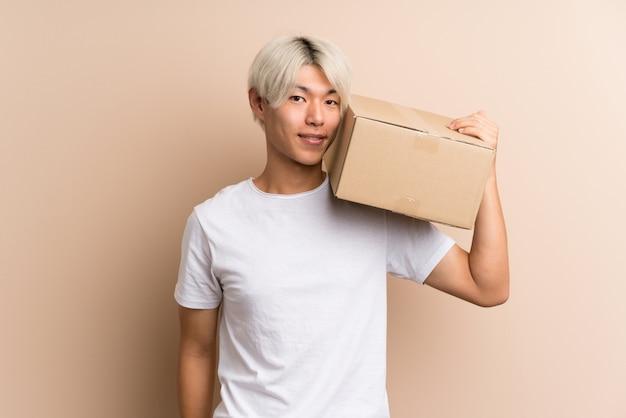 Młody azjatykci mężczyzna nad odosobnionym mieniem pudełko przenosić je do innego miejsca
