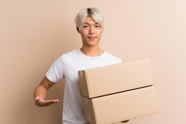 Młody azjatykci mężczyzna nad odosobnionym tłem trzyma pudełko przenosić je do innego miejsca