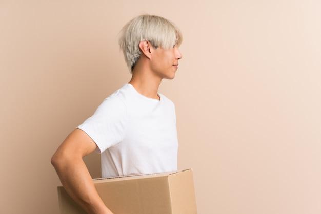 Młody azjatykci mężczyzna nad odosobnionym trzymający pudełko, aby przenieść go do innego miejsca w pozycji bocznej