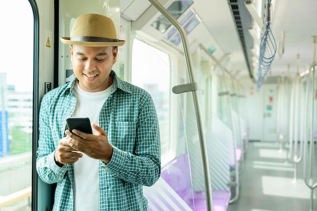 Młody azjatykci mężczyzna ono uśmiecha się używać smartphone w metrze lub niebo pociągu