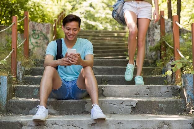 Młody azjatykci mężczyzna outdoors siedzi na drabinowym gawędzeniu telefonem.