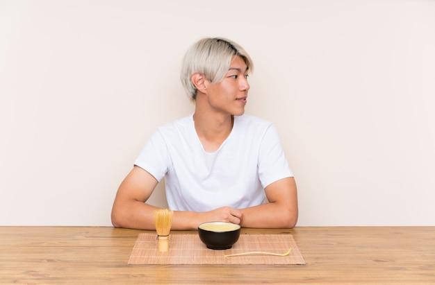 Młody azjatykci mężczyzna patrzeje strona z matcha herbatą w stole