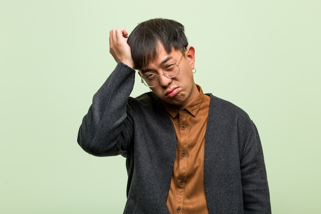 Młody azjatykci mężczyzna przeciw zielonej ścianie
