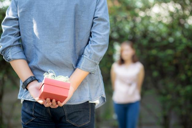 Młody azjatykci mężczyzna trzyma prezenta pudełka niespodziankę jego dziewczyna