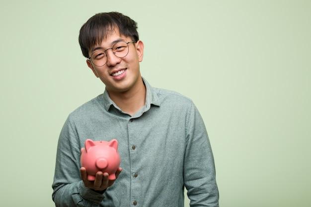 Młody azjatykci mężczyzna trzyma prosiątko banka rozochoconego z dużym uśmiechem
