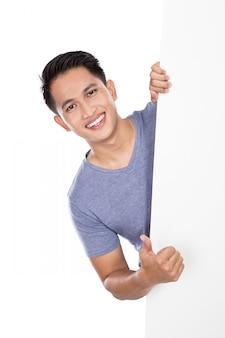 Młody azjatykci mężczyzna trzyma pustego sztandar pokazuje kciuk up
