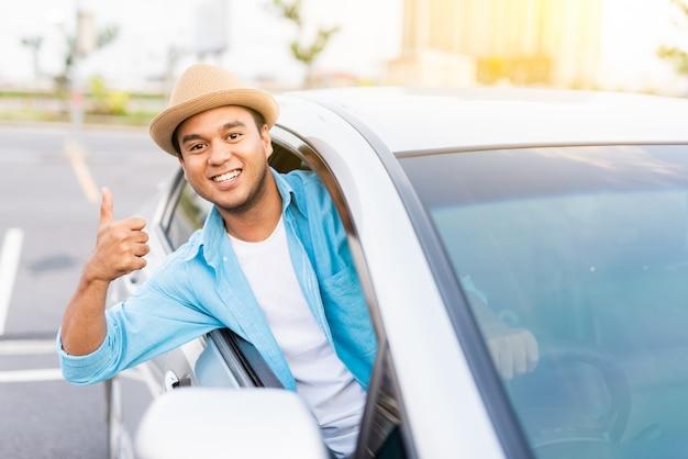 Młody azjatykci mężczyzna uśmiecha się kciuk up i pokazuje up w jego samochodzie.