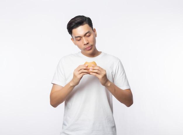 Młody azjatykci mężczyzna w białym koszulki łasowania hamburgerze z szczęśliwą twarzą odizolowywającą na biel ścianie