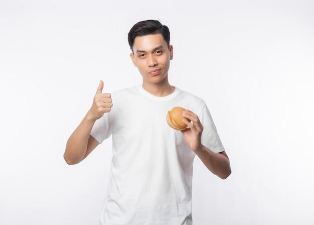 Młody azjatykci mężczyzna w białym koszulki mienia hamburgerze i seans aprobatach odizolowywać na biel ścianie