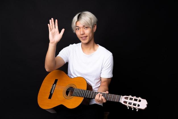 Młody azjatykci mężczyzna z gitarą nad czernią salutuje z ręką z szczęśliwym wyrażeniem