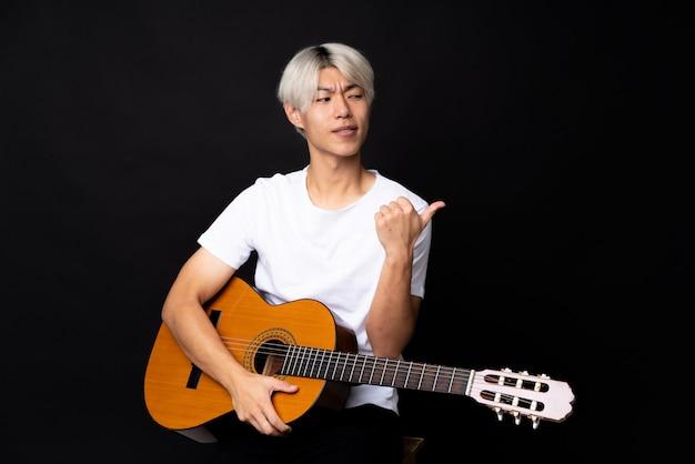 Młody azjatykci mężczyzna z gitarą nad czernią wskazuje z boku przedstawiać produkt