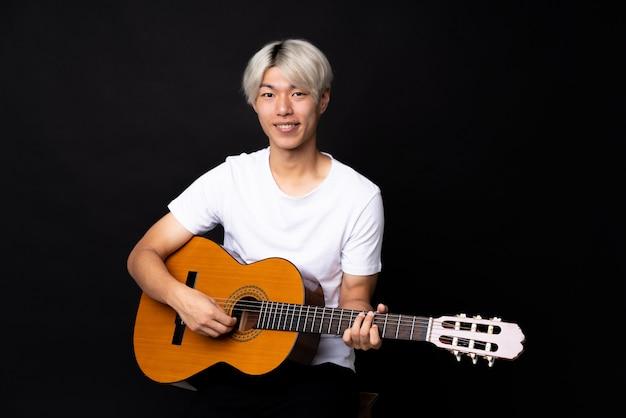 Młody azjatykci mężczyzna z gitarą nad czernią