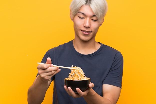 Młody azjatykci mężczyzna z kluskami nad odosobnionym kolorem żółtym