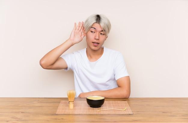 Młody azjatykci mężczyzna z matcha herbatą w stołowym słuchaniu coś