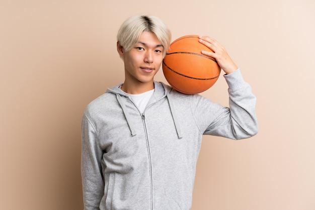 Młody azjatykci mężczyzna z piłką koszykówka
