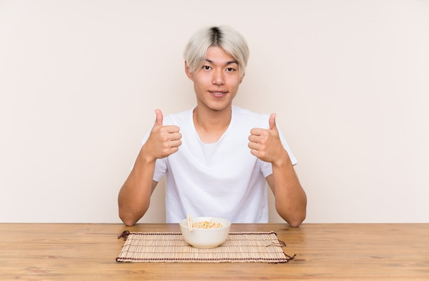 Młody azjatykci mężczyzna z ramen w stole daje aprobata gestowi