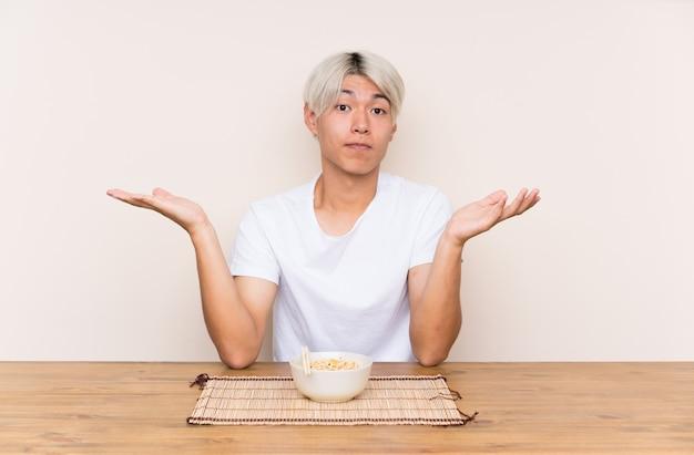 Młody azjatykci mężczyzna z ramen w stole ma wątpliwości z zmieszanym twarzy wyrażeniem