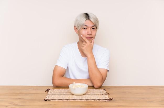 Młody azjatykci mężczyzna z ramen w stołowy śmiać się