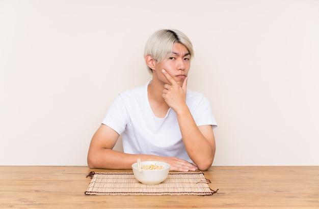 Młody azjatykci mężczyzna z ramen w stołowym główkowaniu pomysł