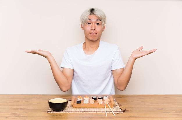 Młody azjatykci mężczyzna z suszi w stole ma wątpliwości z zmieszanym twarzy wyrażeniem