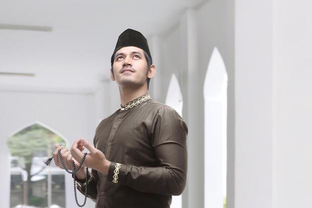 Młody azjatykci muzułmański mężczyzna z modlitewnymi koralikami ono modli się