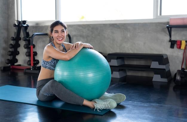 Młody azjatykci ono uśmiecha się sporty przy joga gym