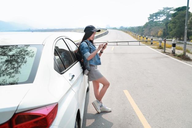 Młody azjatykci podróżnik z samochodem używać mądrze telefon podczas gdy podróżujący podczas wakacje wakacje