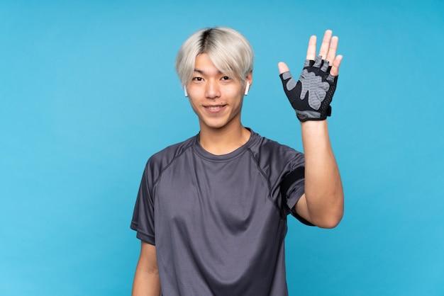 Młody azjatykci sporta mężczyzna nad odosobnionym błękitnym salutuje z ręką z szczęśliwym wyrażeniem