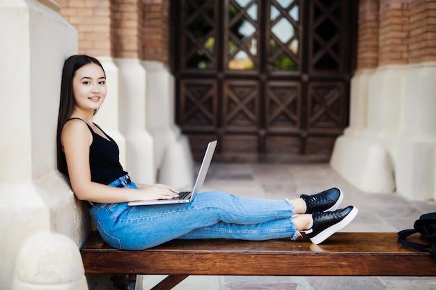 Młody azjatykci student na kampusie uniwersyteckim z komputerowym laptopem