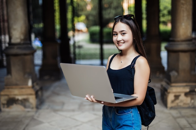 Młody azjatykci student na kampusie uniwersyteckim z laptopem