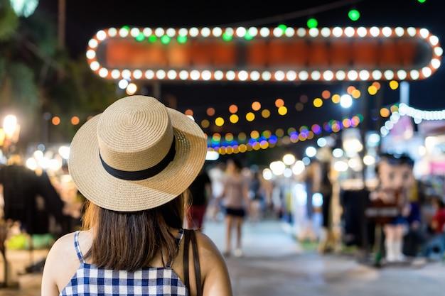 Młody azjatykci turystyczny patrzeć, chodzić i robić zakupy przy ulicznym noc rynkiem ,.