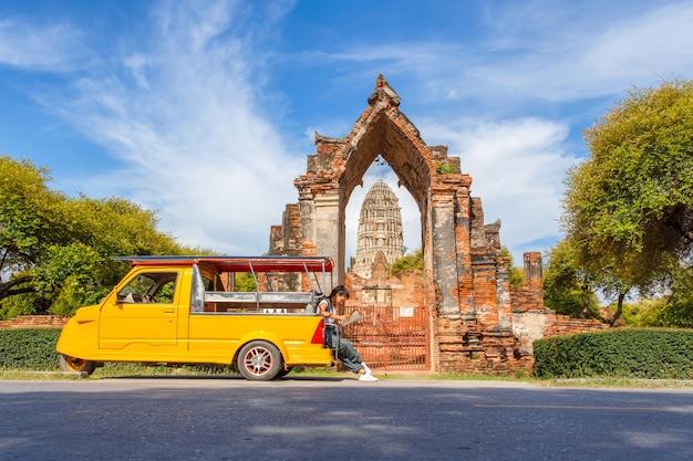 Młody azjatykci żeński podróżnik podróżuje obsiadanie na taxi lub tuk tuk z plecakiem