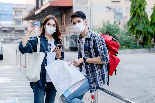 Młody backpacker mężczyzna trzymający papierową mapę i ładna kobieta noszą sombrero, trzymają smartfona i pokazują kartę kredytową w dłoni, używają ich do zapłaty za podróż ze szczęściem na wakacjach