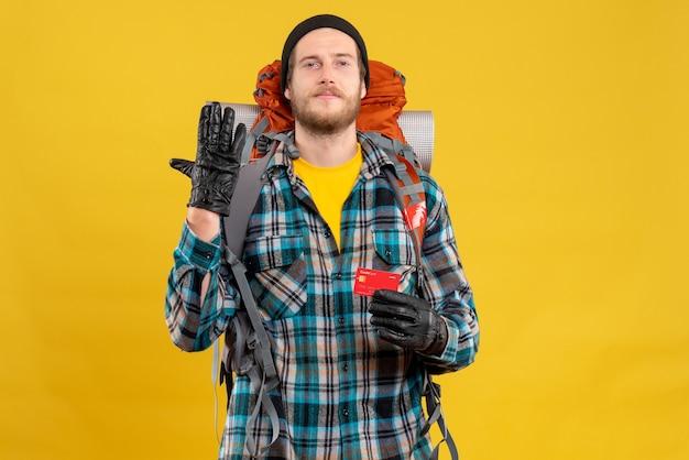 Młody backpacker w czarnym kapeluszu trzymający kartę kredytową