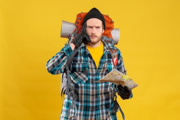 Młody backpacker w czarnym kapeluszu trzymający mapę myślący o czymś