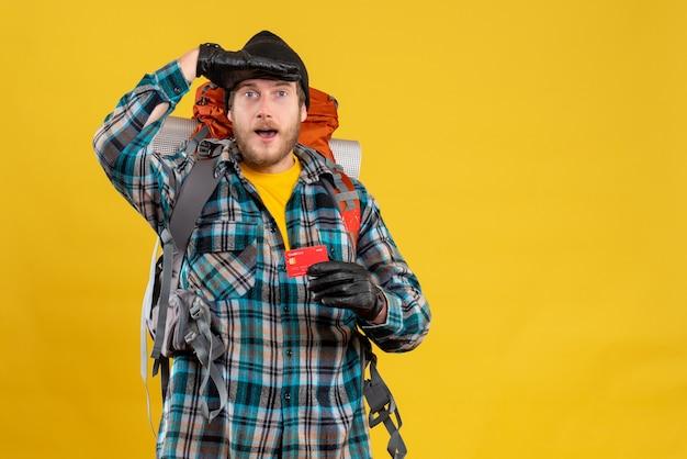 Młody backpacker w czarnym kapeluszu trzymający obserwację karty rabatowej