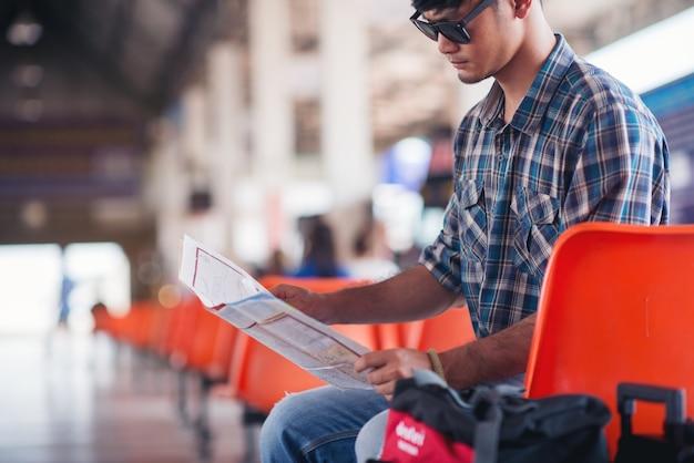 Młody backpacker z kapeluszem i mapa przy dworcem z podróżnikiem