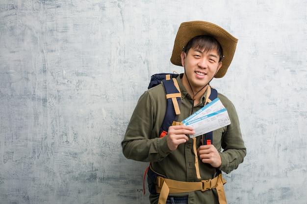 Młody badacz chiński człowiek trzyma bilety lotnicze wesoły z wielkim uśmiechem