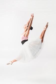 Młody baletniczego tancerza doskakiwanie przeciw białemu tłu