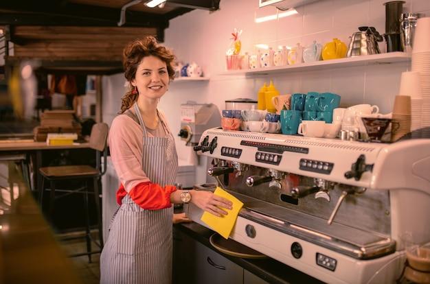 Młody barista. urocza młoda kobieta, wyrażając pozytywność i czyszczenia sprzętu w kawiarni