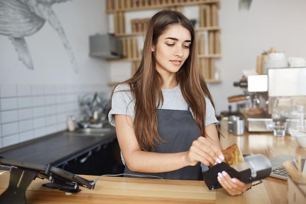 Młody barista używający czytnika kart kredytowych do wystawiania rachunków klientowi. płatności bezprzewodowe to przyszłość handlu.