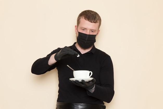 Młody barista w czarnym garniturze ze składnikami i sprzętem do kawy brązowe nasiona kawy w czarnej sterylnej masce na białym tle